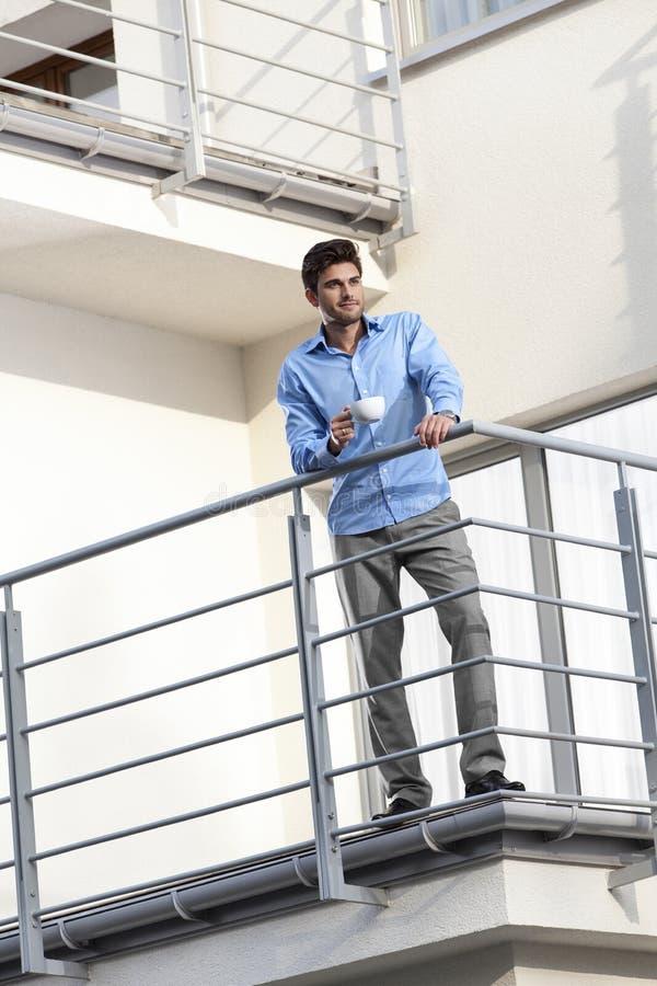 Integrale di giovane uomo d'affari che mangia caffè al balcone dell'hotel immagini stock