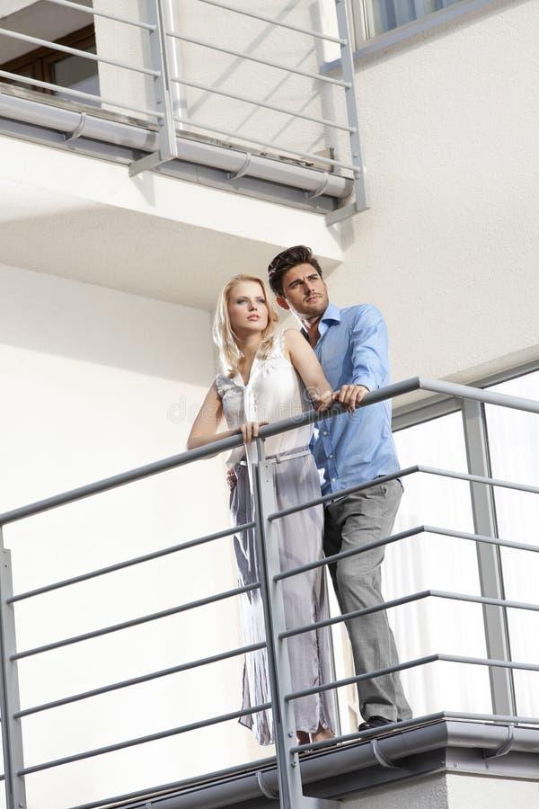 Integrale di giovani coppie che distolgono lo sguardo mentre stando al balcone dell'hotel fotografia stock libera da diritti