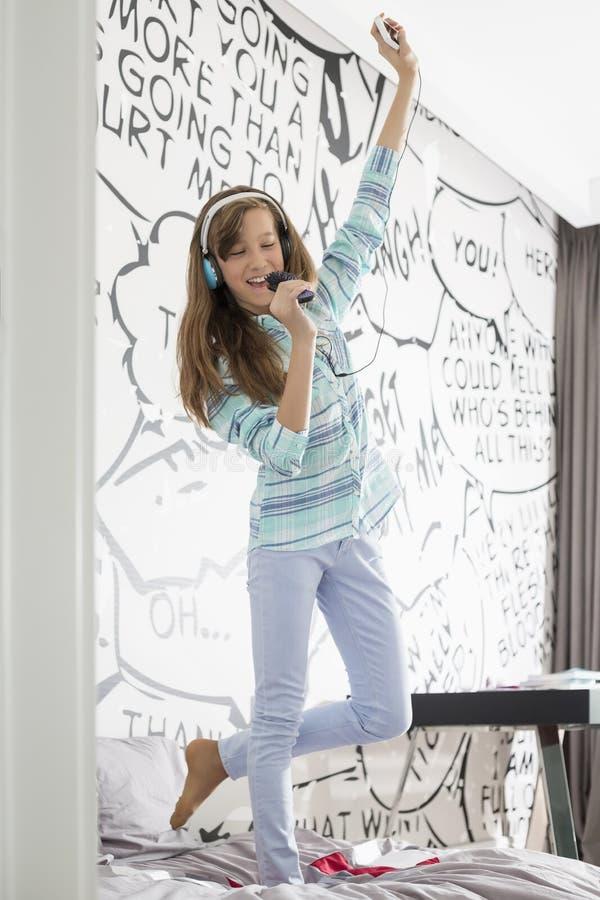 Integrale di musica d'ascolto della ragazza mentre cantando nella spazzola per i capelli sul letto fotografia stock