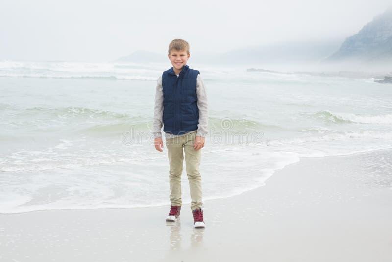 Integrale di un ragazzo sorridente sveglio alla spiaggia fotografie stock