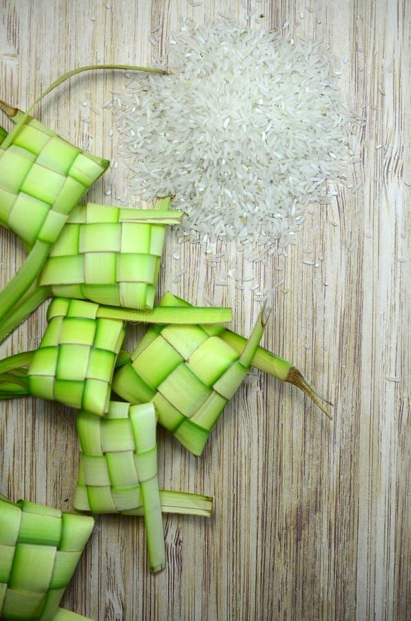 Intelaiatura di Ketupat e riso crudo su fondo di legno immagine stock libera da diritti