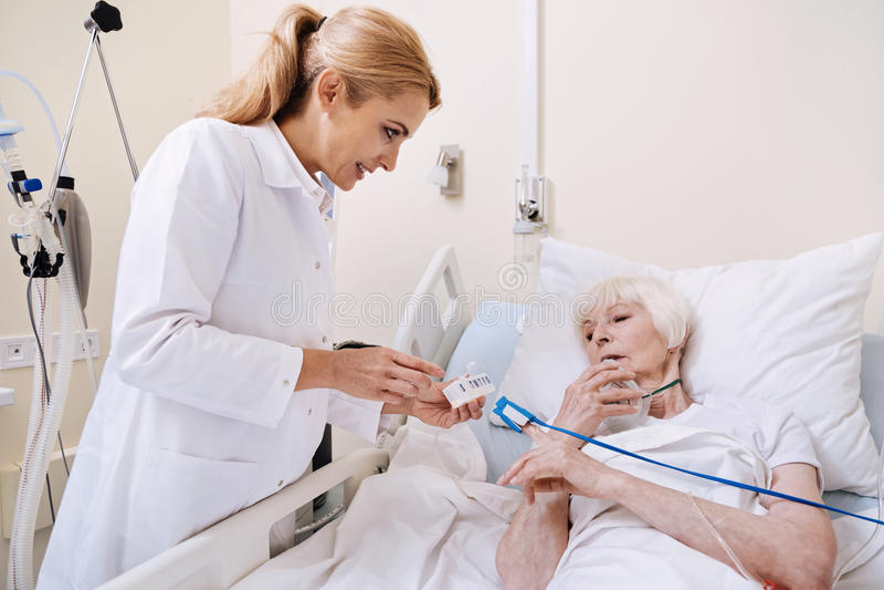 Inteligentna starsza kobieta pyta pytania o lekarstwie zdjęcie stock