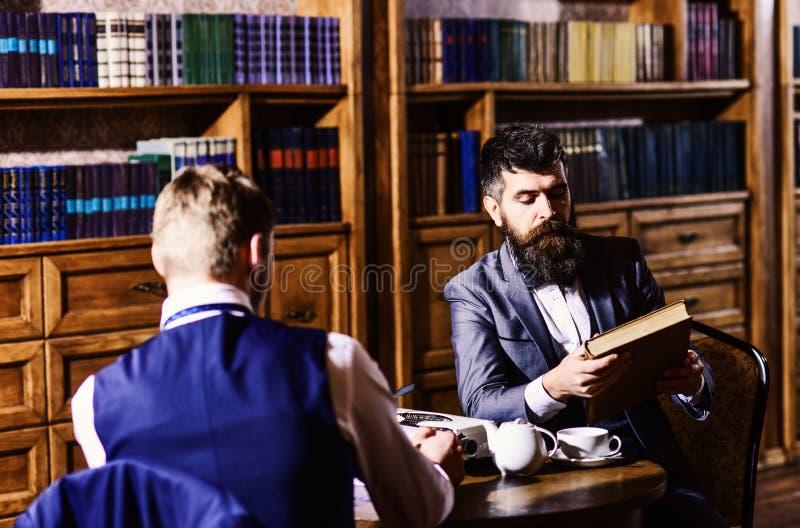 Inteligentni mężczyzna, naukowa spotkanie w bibliotece Mężczyzna w kostiumu zdjęcie royalty free