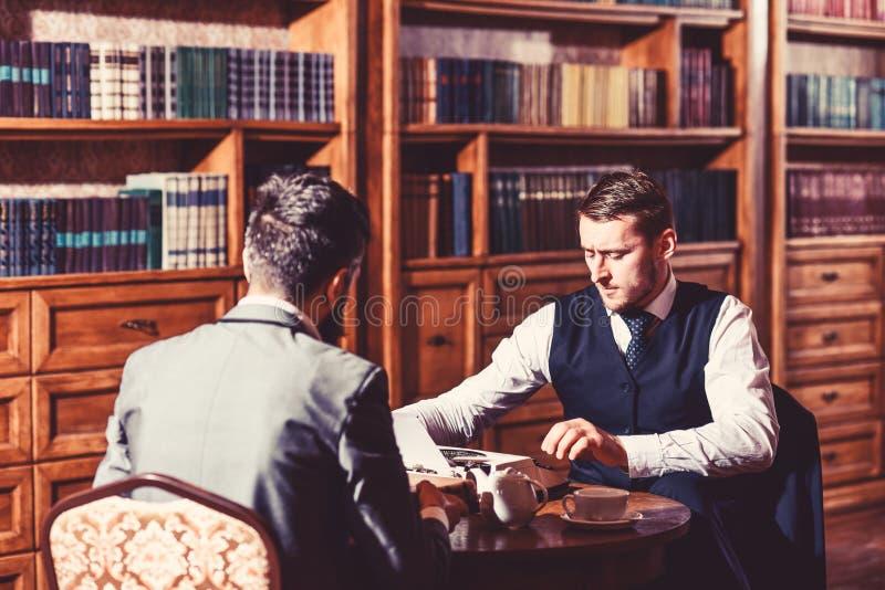 Inteligentni mężczyzna, naukowowie wydają czas wolnego w bibliotece obrazy royalty free
