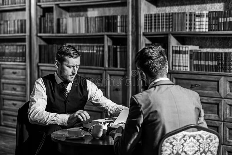 Inteligentni mężczyzna, naukowowie wydają czas wolnego w bibliotece zdjęcia royalty free