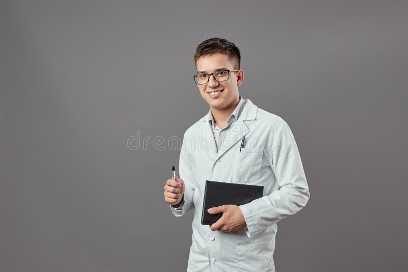 Inteligentny uśmiechnięty facet w szkłach ubierających w białym żakiecie trzyma notatnika i nieckę na szarym tle zdjęcie stock