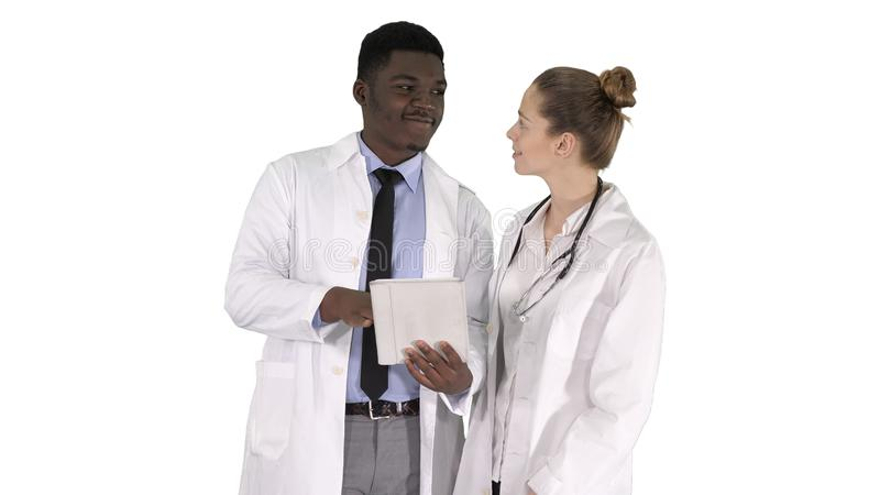 Intellectual healthcare professional afro american doctor with collegue using digital tablet on white background. stock photo