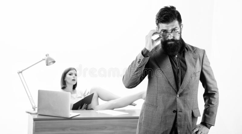 An intellectual look of hipster. Hipster fixing his glasses while sexy woman working in background. Bearded hipster and stock images