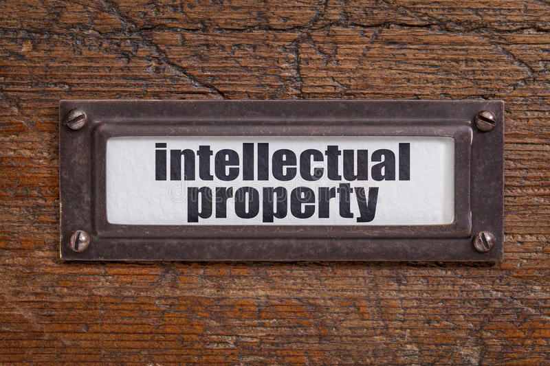 Intellectual property label. Intellectual property - file cabinet label, bronze holder against grunge and scratched wood royalty free stock image