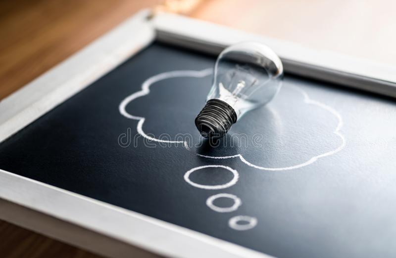 Intellectual property, new idea, psychology or brainstorm concept. Creativity, innovation and inspiration. Energy consumption. Light bulb on blackboard with stock images
