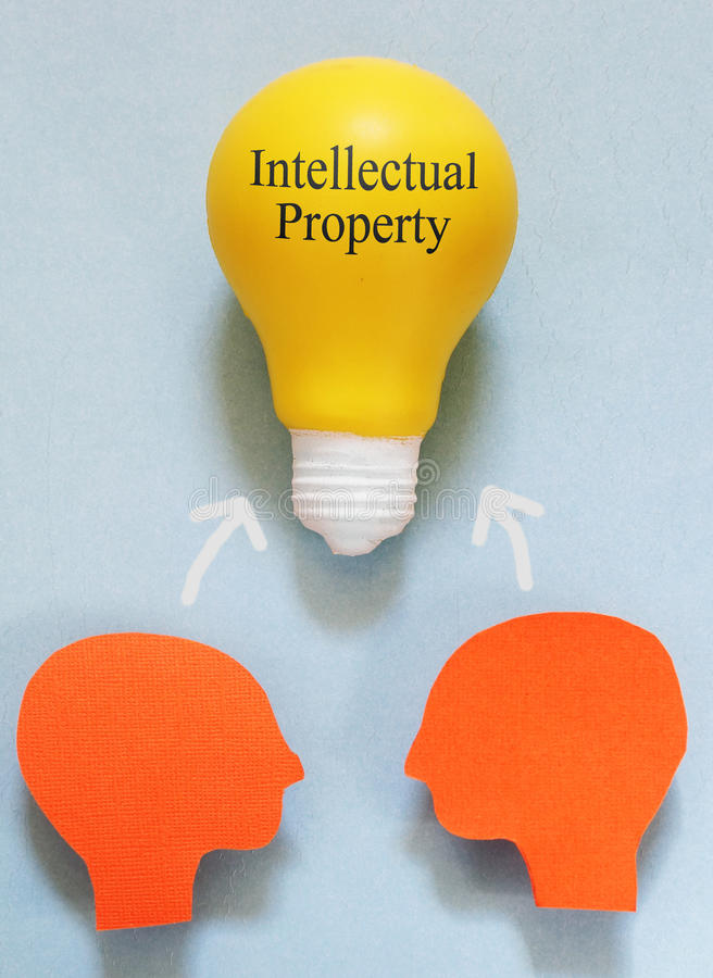 Intellectual Property. Two paper heads with a IP light bulb - Intellectual Property concept royalty free stock photography