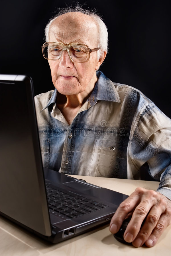 Intellectual senior man. Works on the laptop late at night stock photos