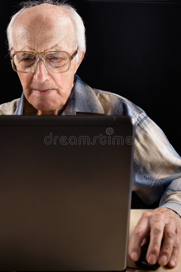 Intellectual senior man. Works on the laptop late at night royalty free stock photo