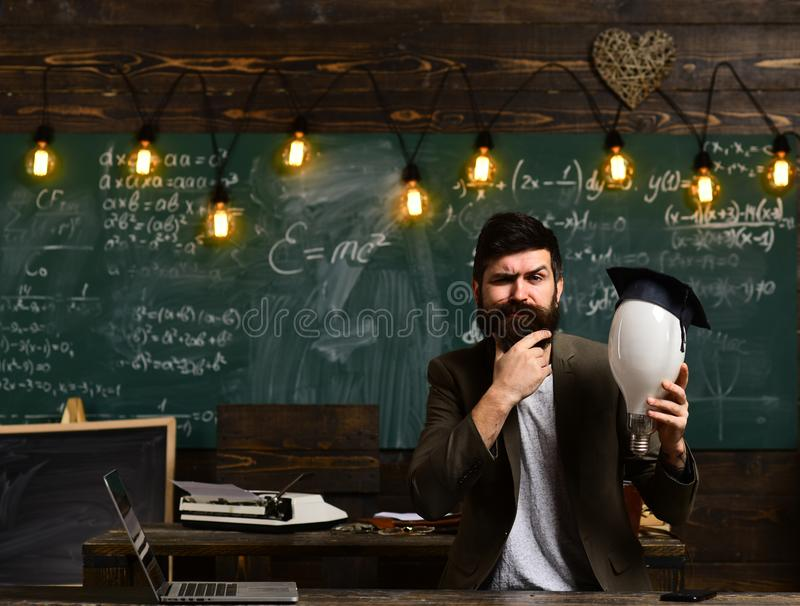 Intellectual task concept. Bearded hipster with bulb and chalkboard on background. Guy thinking with thoughtful. Expression. Man with beard and mustache on stock photo