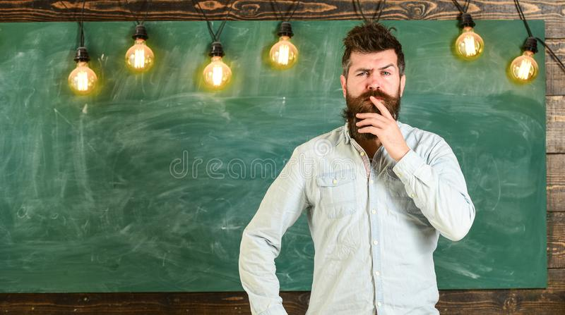 Intellectual task concept. Man with beard and mustache on thoughtful face stand in front of chalkboard. Bearded hipster royalty free stock photo