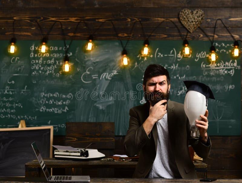 Intellektuellt uppgiftsbegrepp Skäggig hipster med kulan och svart tavla på bakgrund Grabb som tänker med fundersamt arkivfoto