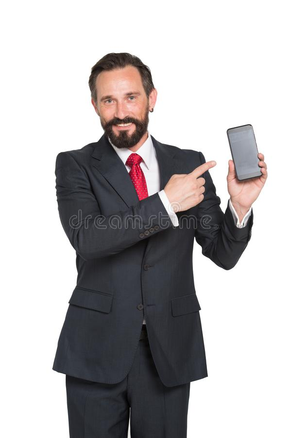 Intelligent bearded manager presenting latest smartphone model. Positive bearded mature manager pointing at the latest smartphone model while smiling and making royalty free stock photography