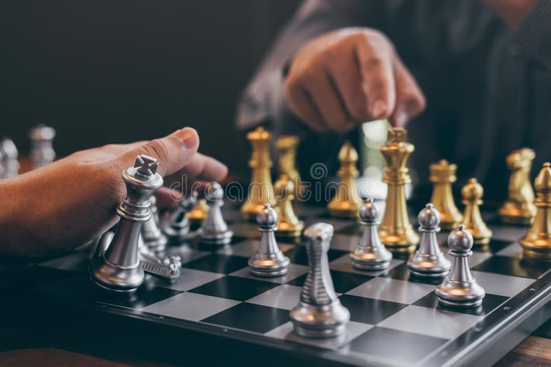 Intelligent businessman playing chess game competition with the opposite team, planning business strategic to development for win. And success, Gold and silver stock photography