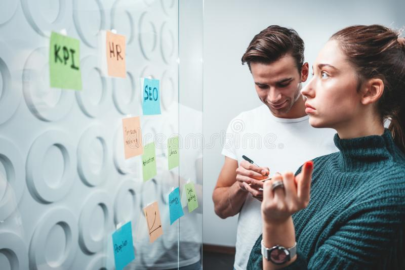 Intelligent coworkers people brainstorming new business plan posted on a sticky glass note wall royalty free stock photos