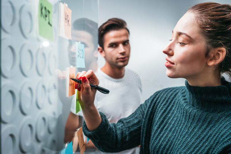 Intelligent coworking people preparing business strategy and posted on a sticky glass note wall. Manager team brainstorming on new business ideas royalty free stock photos