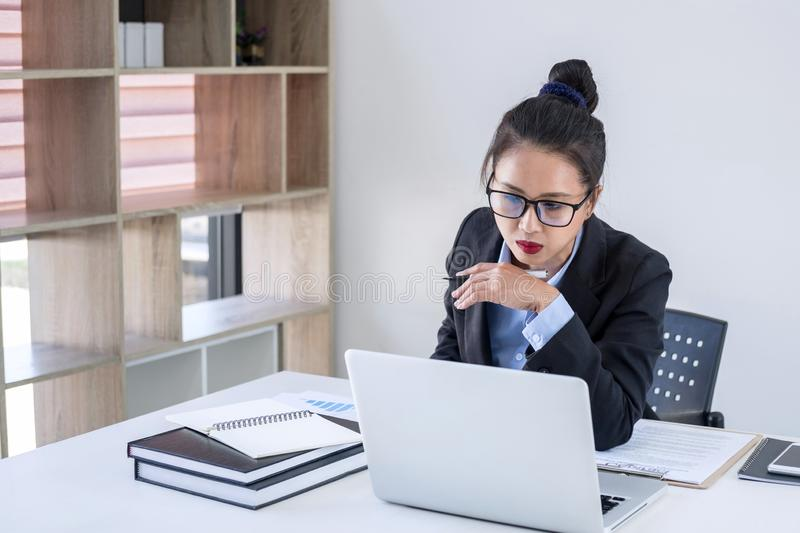 Intelligent female businesswoman working on laptop while analysis business strategy and sale performance contract on workplace royalty free stock photography