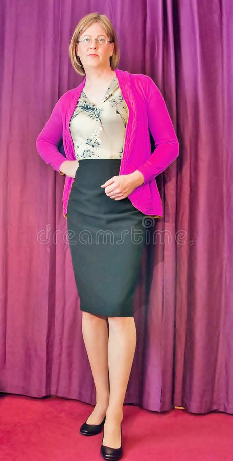 Intelligent gekleidete mittlere Greisin, die eine rosa Wolljacke und schwarzen einen Bleistiftrock trägt stockbild