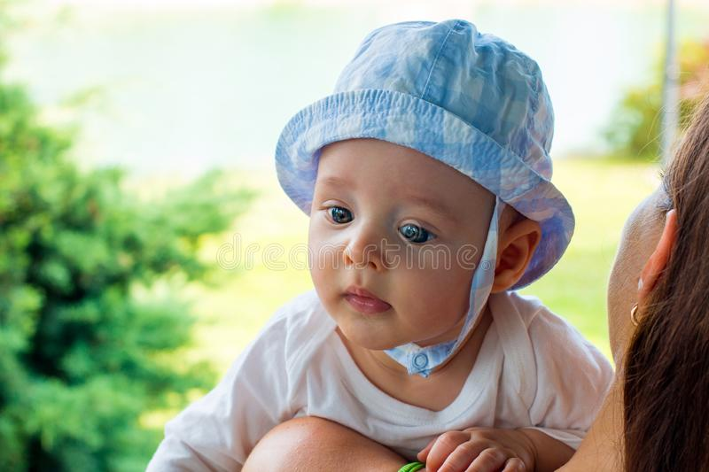 Baby in cap on little head with fascinated face and focused blue eyes resting above mother's shoulder outside in nature royalty free stock image