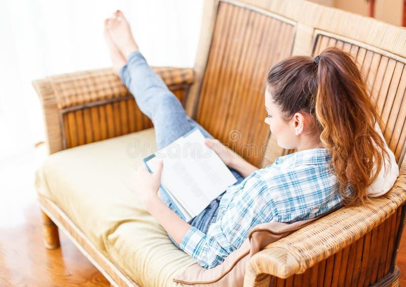 Intelligent kvinna som läser en bok på soffan royaltyfria bilder