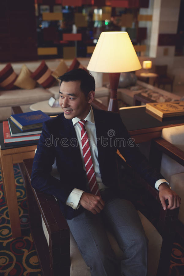 Intelligent managing director relaxing after meeting in armchair of his private office room royalty free stock photography