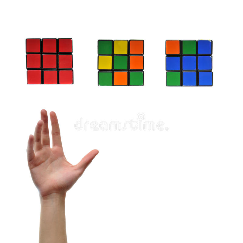 Intelligent Qube. Hand reaching up for red puzzle cube isolated on white background. You must contact Seven Towns Ltd for permission prior to any use of any of stock photos