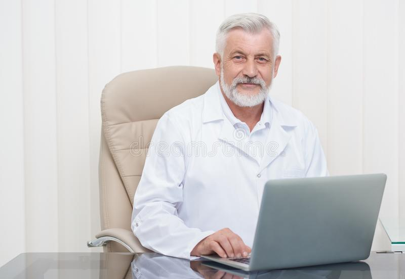 Intelligent senior doctor working on laptop in office. stock images