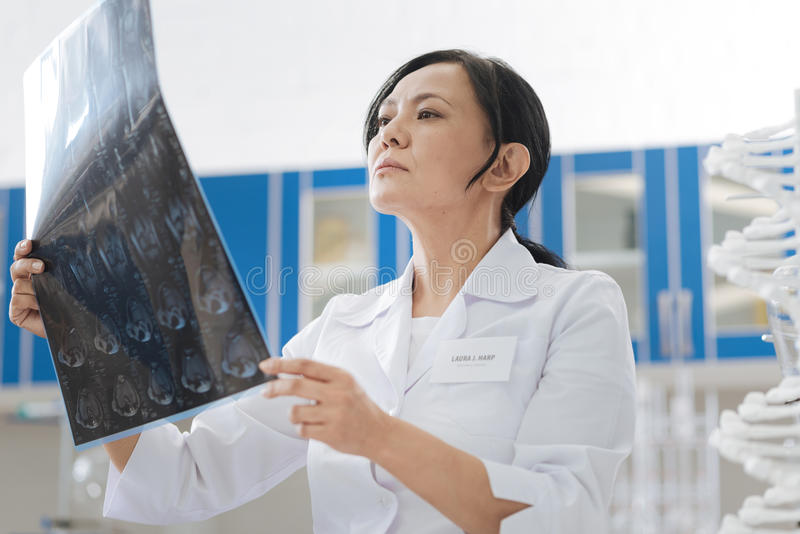 Intelligent skillful doctor examining an X ray photo. Interesting case. Intelligent skillful professional doctor holding an X ray photo and examining it while stock photos