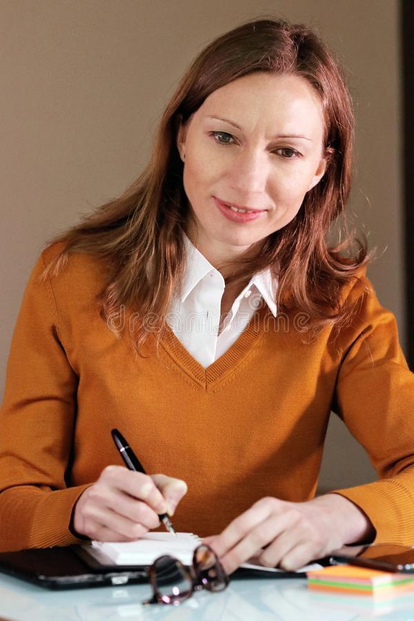 Intelligent woman taking business notes stock photo