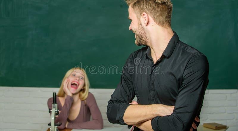 Intelligent und hohes ausgebildet Stehende Hände des gut aussehenden Mannes kreuzten im Klassenzimmer mit Lehrer Hohe Schülerspre stockbild