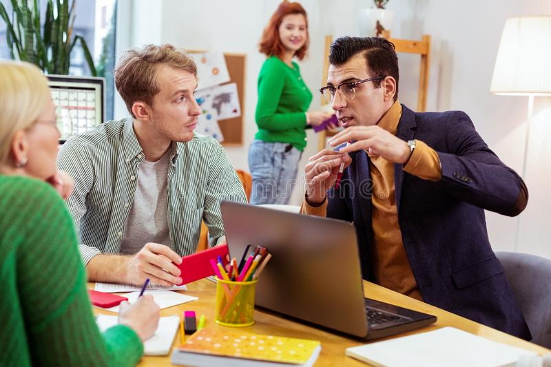 Intelligent young man sharing his knowledge with colleagues royalty free stock image