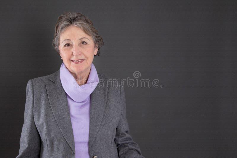 Intelligente ältere Frau mit dem grauen Haar auf grauem Hintergrund lizenzfreies stockbild
