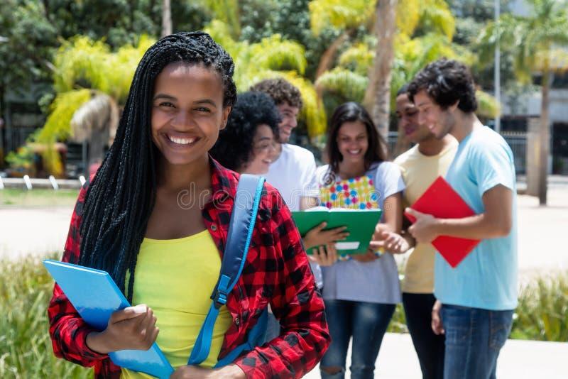 Intelligente Afroamerikanerstudentin mit Gruppe Studenten lizenzfreie stockfotos