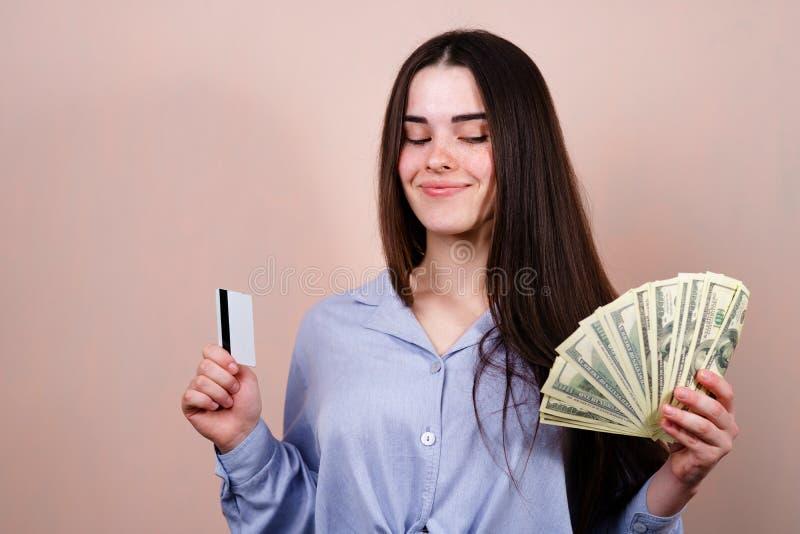 Intelligente Frau mit Kreditkarte und Dollarscheinen stockfotos