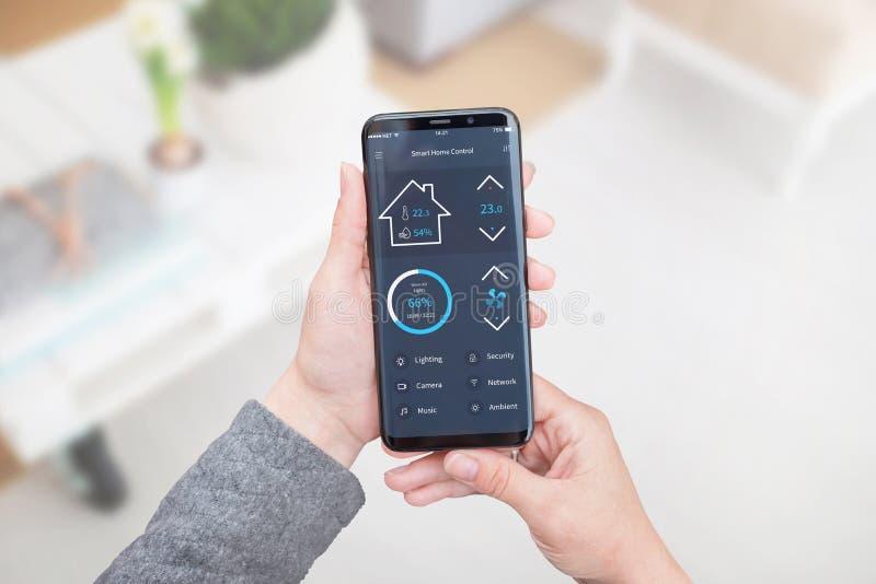 Intelligente Hauptsteuerapp für tragbare Geräte in der Frauenhand Wohnzimmerinnenraum im Hintergrund lizenzfreies stockbild