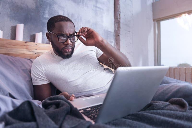 Intelligente jonge Afrikaanse Amerikaanse mens die thuis freelancing royalty-vrije stock foto's
