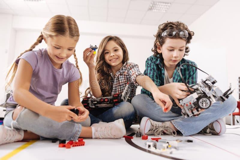 Intelligente kinderen die gadgets en apparaten in de studio met behulp van stock foto's