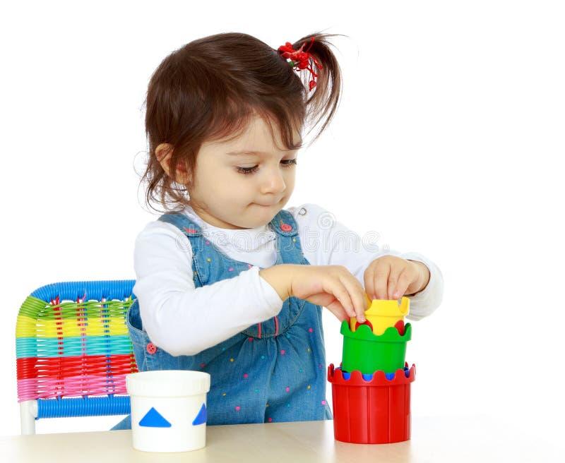 Intelligente Mädchenspiele, die am Tisch sitzen stockfoto