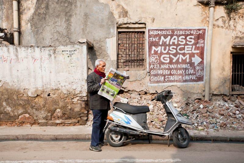 Intelligente mens die het recentste nieuws in een krant lezen, die zich op vuile straat van stad bevinden royalty-vrije stock foto's