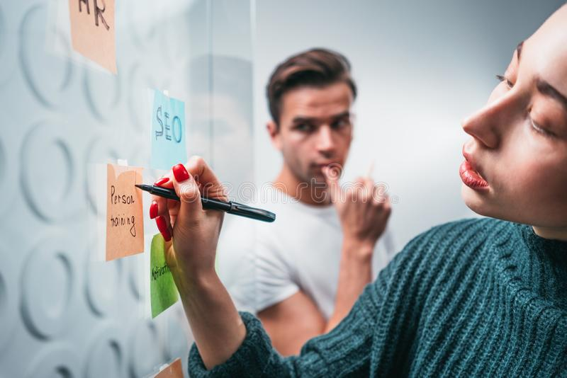 Intelligente Mitarbeiterleute, die den neuen Unternehmensplan bekannt gegeben auf einer klebrigen Glasanmerkungswand brainsorming stockfoto