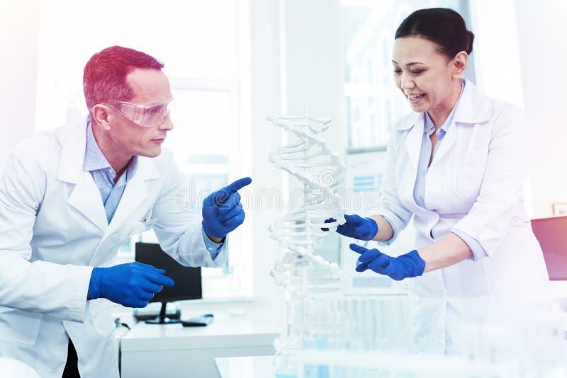 Intelligente slimme mensen die menselijk genoom in het laboratorium bestuderen stock foto's