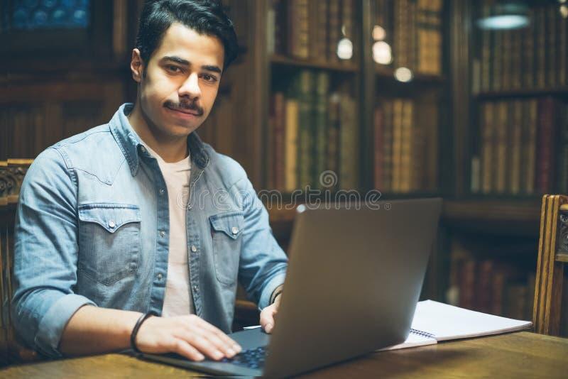 Intelligente Studienstimmung Junger arabischer Mann, der in der Bibliothek arbeitet stockbild