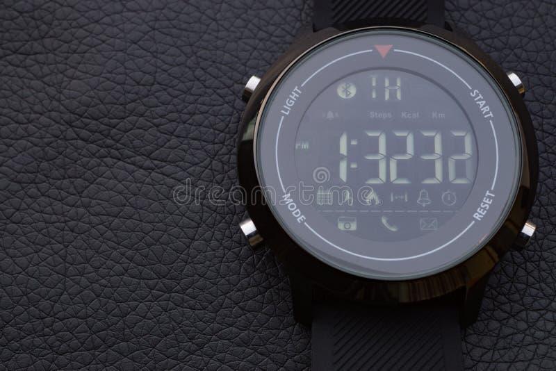 Intelligente Uhren des Sports auf schwarzem Leder lizenzfreies stockfoto