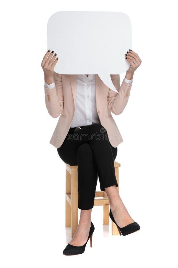 Intelligente zufällige Frau hält Spracheblase vor Gesicht stockbild