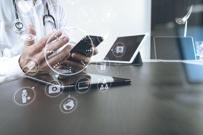 intelligenter Arzt, der mit intelligentem Telefon und digitaler Tablette arbeitet stockfotos