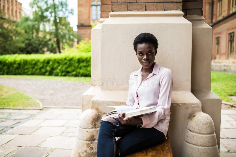 Intelligenter des Afroamerikaners Student uni, der ein Buchfreien am Campus liest stockfotos